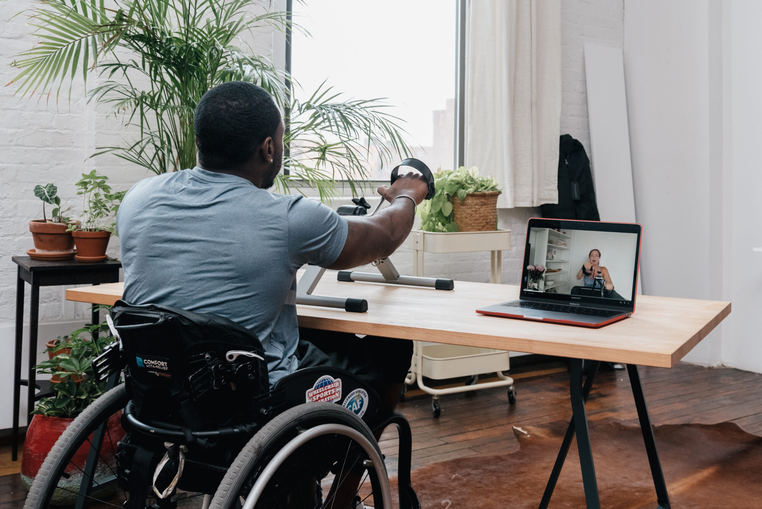 A man in a wheelchair using a handcycle exercising to a Kakana crosscycle class on his computer.