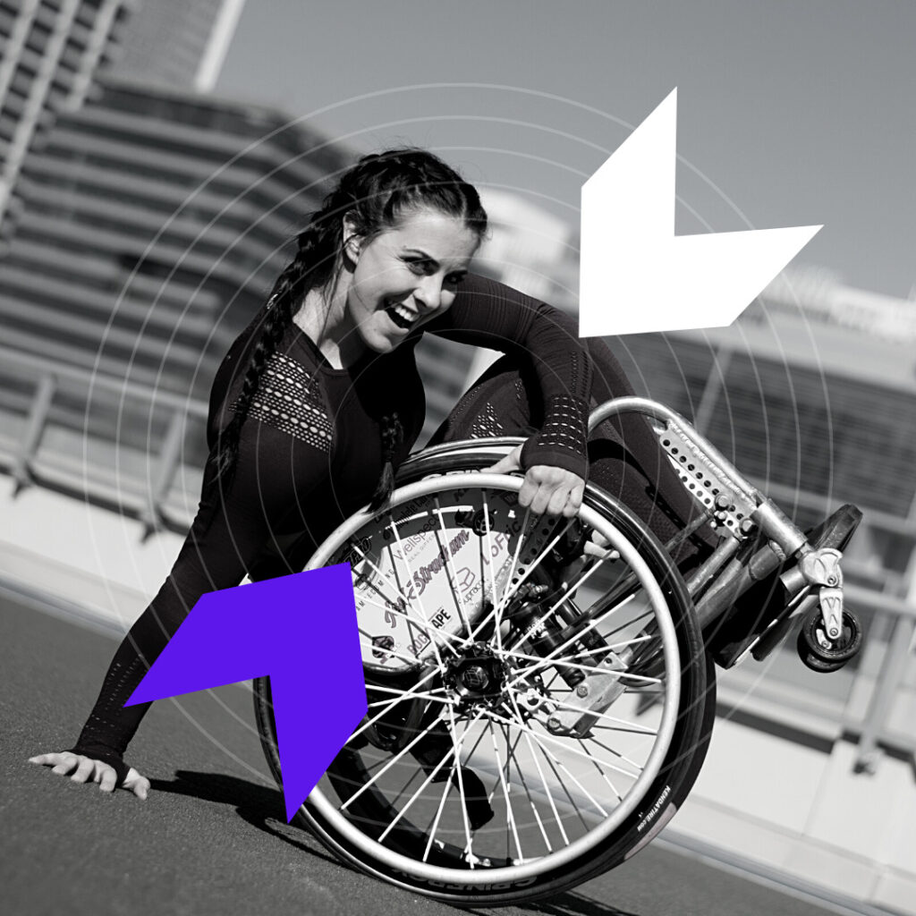 Jesi is leaning back in her wheelchair with the front wheels in the air and her right hand on the ground.